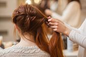 Beautiful with long red-haired hairy girl hairdresser weaves a French braid in a beauty salon. Professional hair care and creating hairstyles. poster