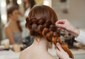 Beautiful with long red-haired hairy girl hairdresser weaves a French braid close-up in a beauty salon. Professional hair care and creating hairstyles. poster
