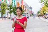 Asian woman outside on Wangfujing shopping street in Beijing, China, using mobile phone app to shop online. Happy Chinese woman texting sms on smartphone. poster