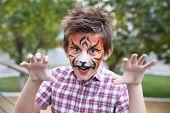 Cute little boy with aqua makeup of tiger muzzle poster