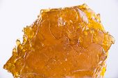 Big piece of cannabis oil concentrate aka shatter isolated over white background poster