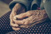 Old Asian female hands full of freckles and wrinkles at the age of more than 80 years old / Aging concept poster