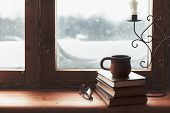 Warm and comfy winter concept. Book, cup of tea and candlestick on wooden window sill in old house. Reading and relaxing in cold snowy weather at home. Quiet silent homely scene. poster