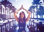 Pretty Indian woman practicing yoga on summer vacation standing meditating with closed eyes at the end of a long tranquil resort pool lined with tropical palms in a healthy lifestyle or travel concept poster