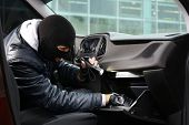 Male thief stealing valuables from car poster