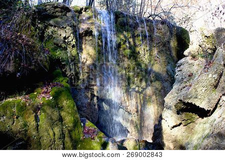 Waterfall In The Forest In Autumn. Dry Trees, Green Moss And Thin Streams Of Clear Water In The Wate