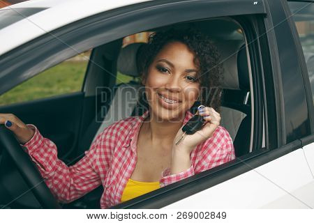 Young Asian Woman In Car.modern Young Girl Driver Drives A Car And Looks Away With A Smile With Brac