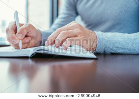 Man Writing In Hid Personal Organizer. Planning And Information Structuring.