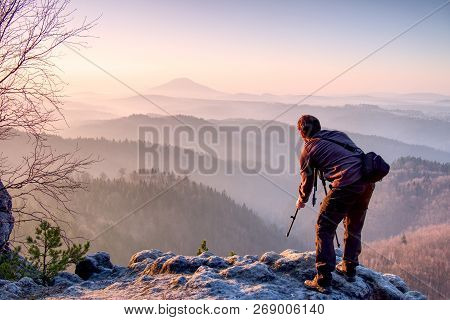 Outdoor Photographer With Tripod And Camera On Rock Thinking. Thick Fog In Autumnal Countryside. Man