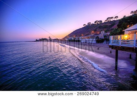 Scenic Coastal Landscape With Santa Monica Mountains And Surfrider Beach At Dusk Iluminated By Night