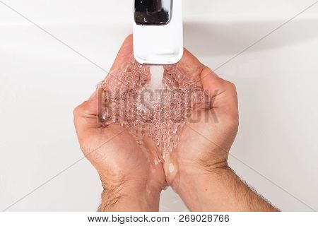 Man Wetting Hands Under Inox Tap Close-up As Personal Hygiene Concept