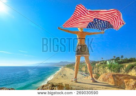 Woman Holding An American Flag In The Blue Sky From Point Dume Promontory On Malibu Coast In Ca, Uni
