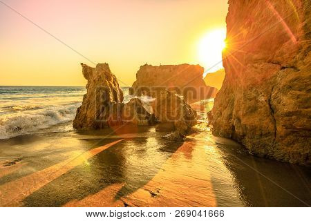 El Matador State Beach, California, United States. Sunbeams With Sunset Lights Between Pillars And R