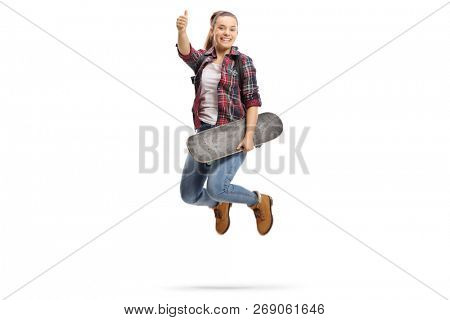 Full length portrait of a joyful teenage girl with a backpack and a skateboard making a thumb up gesture isolated on white background