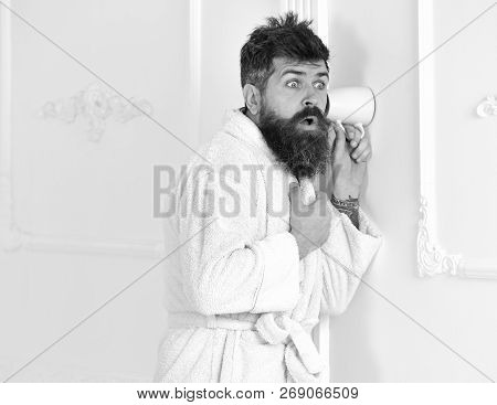 Man With Beard And Mustache Eavesdrops Using Cup Near Wall. Hipster In Bathrobe On Surprised Face Se