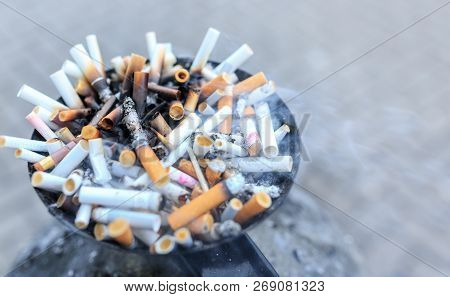 Cigarette butts at ashtray. Close up heap of many smoking cigarettes stubs, cigarette butts in ashtray poster