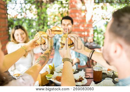 Pals raising hands to toast cheeseburgers during reunion party at restaurant poster
