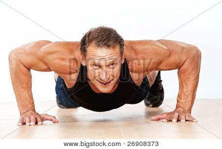 Handsome muscular man doing push-up poster