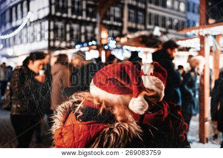 Evening City Scene With Two Women Wearing Red Santa Hats Talking In Center Of The Christmas Market -