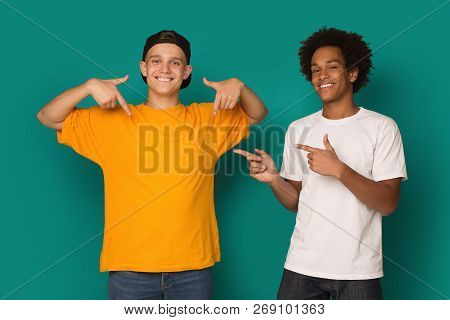 Diverse Teens Pointing At Blank T-shirt Over Blue Background, Copy Space