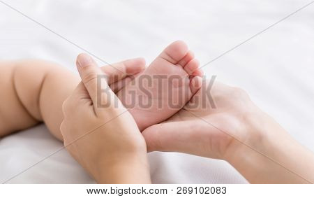 Maternal Protection And Love. Mother Holding Tiny Baby Foot In Hands Closeup