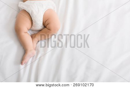 Baby Legs And Bottom In Diaper On White Bed Background, Top View, Copy Space