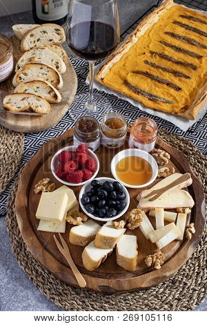 Served Table - Wine Appetizer, Cheese Assortment On Round Wooden Board, Walnuts, Berries, Honey, Jam