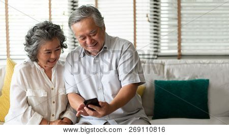 Happy Asian Senior Couple Using Smartphone Technology While Smiling And Sitting On Couch At Their Ho