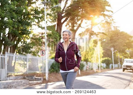 Smiling senior woman jogging on streets in early morning. Active mature woman running on a sunny day while listening to music. Lady running with armband and listening to music at sunset.