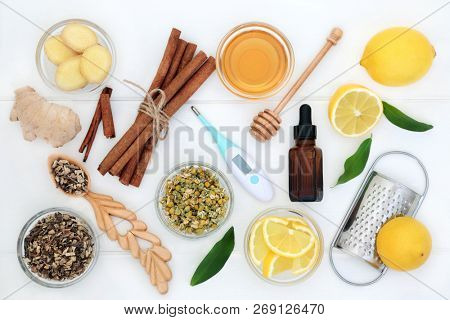 Natural flu and cold remedy ingredients with thermometer, echinacea herb, eucalyptus oil, fresh ginger, lemon fruit, cinnamon sticks and honey on white wood table background. Flat lay.