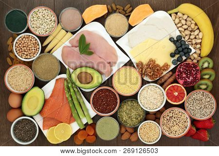 Health food for body builders high in protein including lean meat, salmon, dairy, dietary supplement powders, and tablets, pulses, grains, cereals, nuts and seeds. Top view on oak wood background.