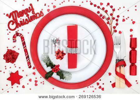 Christmas dinner place setting with Merry Christmas sign, porcelain plates, bauble decorations, napkin, cutlery, winter flora and heart sprinkles on white wood table background.
