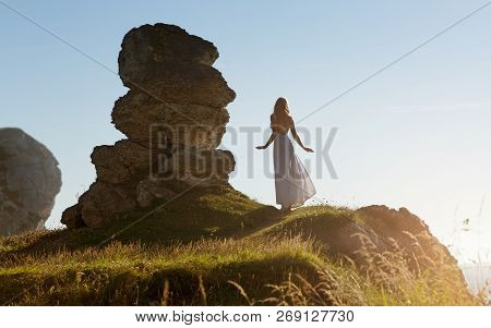 Beautiful Slim Woman In White Long Dress Stands Next To A Strange Rock Formation In Ireland.