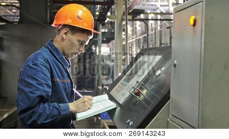 Russia, Angarsk - June 8, 2018: Operator Monitors Control Panel Of Production Line. Manufacture Of P