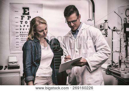 Optometrist discussing eye test report with female patient in ophthalmology clinic