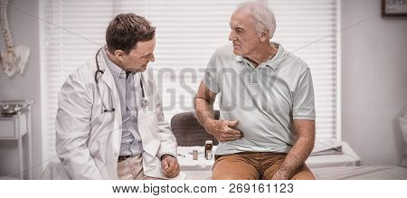 Senior man showing stomach ache pain to doctor in clinic