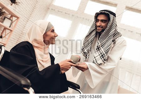 Young Arabian Man Giving Cup To Wife On Wheelchair. Arabian Family Concept. Sitting On Wheelchair. D