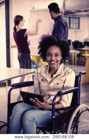 Portrait of smiling disabled business executive in wheelchair using digital tablet in office
