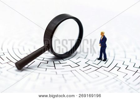 Miniature People: Businessman Use Magnifying Glass To Find The Route On The Maze. Concepts Of Findin
