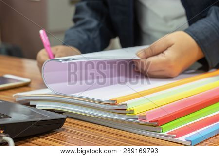 Teacher Hand Is Holding Pen For Checking Student Homework Assignments On Desk In School. Unfinished