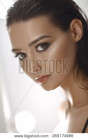 Beautiful Young Woman With Clean Fresh Skin And Perfect Make-up Looking At Camera Agaist White Light
