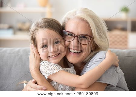 Happy Older Grandmother Hugging Little Grandchild Girl Looking A