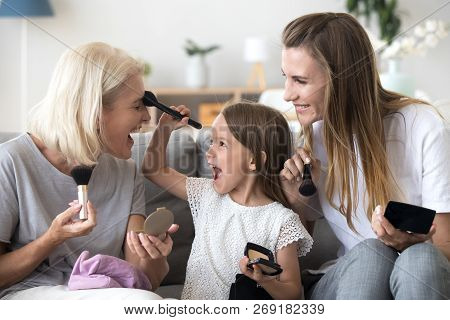 Excited granddaughter puts powder on grandma doing make-up  poster