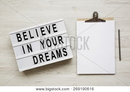 'believe In Your Dreams' Word On Modern Board, Noticeboard, Pencil Over White Wooden Surface, Overhe
