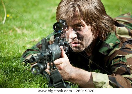 soldier in the field aiming the gun