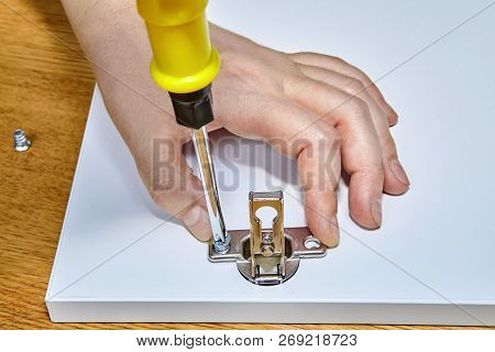 The Furniture Assembler Tightens The Screw In The Furniture Door Hinges On The Surface Of The Wooden