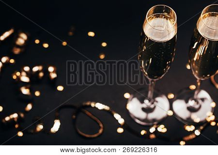 Two Glasses Of Champagne With Golden Decoration On Black Elegant Background. Top View, Place For Tex