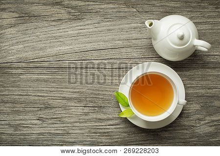 Cup Of Green And Herbs Tea Served With Tea Pot On Wooden Table