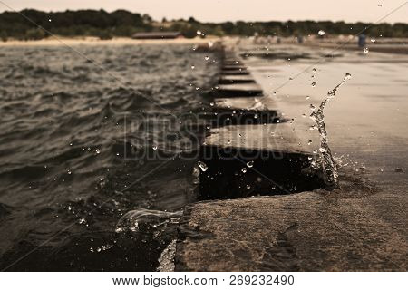 The Splash Of Wave On Jetty Pier With Metal Bollards. Water Splashing During The Overcast Weather. S