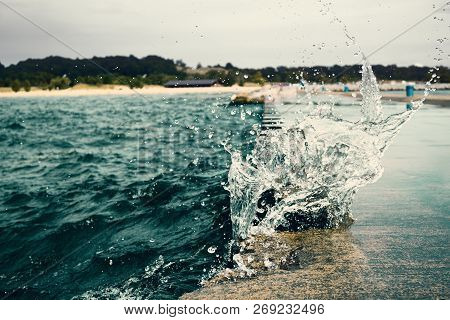 Waves Hit The Stone Sea Pier. Water Splashing During Stromy Weather. Splashes Froze Over The Pier. U